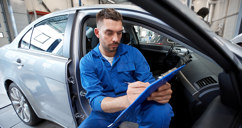 Mechanic in a car checking off a clipboard
